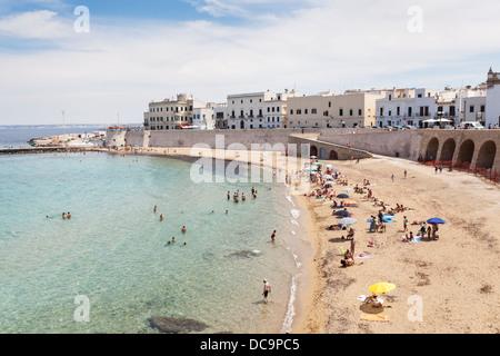 Sandstrand mit bunten Sonnenschirmen an einem sonnigen Sommertag im historischen Zentrum in Gallipoli, Apulien, - Stockfoto