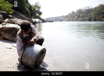 Ein indischer Mann reinigt einen großen Kochtopf in den Fluss Ganges in Rishikesh, Indien. - Stockfoto