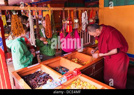 Touristen suchen Schmuck als Mönch auf einige Perlen Schmuck im Kloster Drepung arbeitet; Lhasa, Tibet, Xizang, - Stockfoto