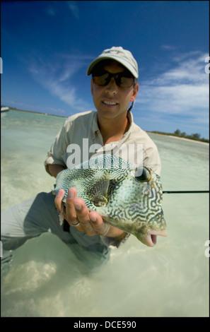 Mann, der ein Kofferfisch hält; Bahamas - Stockfoto