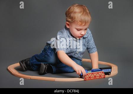 Jungen spielen mit Spielzeugeisenbahn - Stockfoto