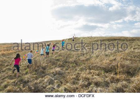 Kinder zu Fuß bergauf mit Windräder und Windmühlen - Stockfoto