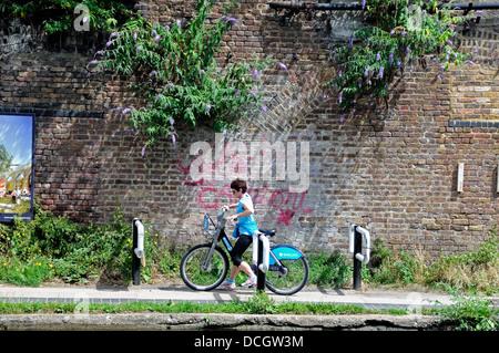 Weibliche Radfahrer auf Barclays Cycle oder Boris Bike Schikane auf die Regents Canal Leinpfad installiert zu verhandeln, - Stockfoto
