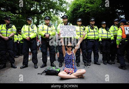 Balcombe, West Sussex, UK. 18. August 2013.  Junge Frau setzt sich halten ein Plakat vor der Polizeiabsperrung als - Stockfoto