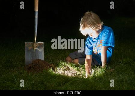 Kind junge einen Schatz in magische Loch im Boden zu graben, in der Dämmerung - Stockfoto