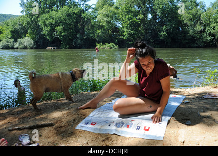 Junge Frau beim Sonnenbaden Fluss Lot mit Hund Wasser abschütteln, in der viele Region oder Abteilung der Süd-West - Stockfoto