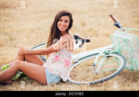 Schönen Lächeln Mädchen sitzt neben Fahrrad in Landschaft, Sommer-Lifestyle - Stockfoto