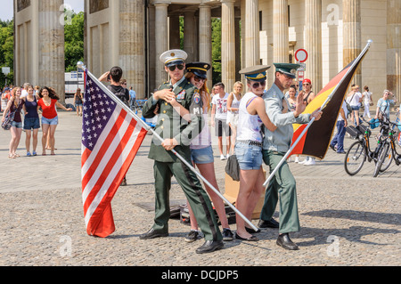 2 junge Frauen mit Visor Caps und 2 Soldaten mit amerikanischer und deutscher Flagge posiert vor dem Brandenburger - Stockfoto