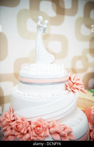 süße Hochzeitstorte mit roten Blüten und Porzellan Braut und Bräutigam an der Spitze - Stockfoto