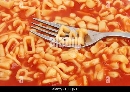 Gabel mit Alphabet Spaghetti Schreibweise auf einem Hintergrund von gemischten Alphabet Spaghetti Essen - Stockfoto