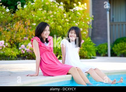 Zwei junge Mädchen sitzt neben Schwimmbad, Lächeln - Stockfoto