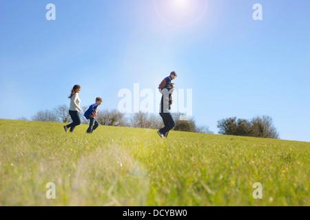 Familie läuft auf Feld - Stockfoto