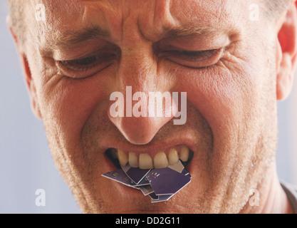 Wütend enttäuschter Mann mit Cut-Up-Kreditkarte im Mund; Torremolinos, Malaga, Andalusien, Spanien - Stockfoto