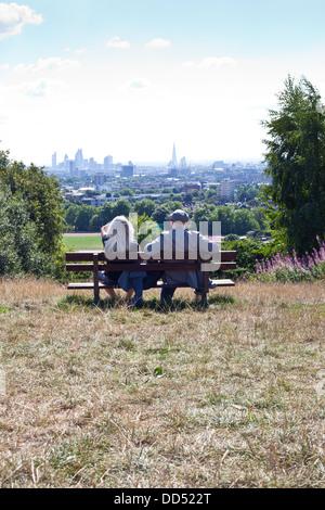 Paar auf Bank Blick auf Skyline von London vom Parliament Hill, Hampstead Heath - Stockfoto