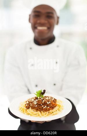 Afrikanische männlichen Chef Spaghetti in modernen Küche präsentiert - Stockfoto