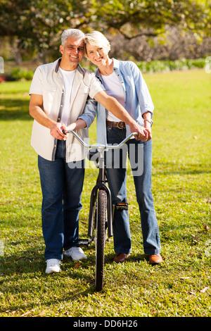 fröhliche mittleren gealterten paar zu Fuß ein Fahrrad in der Natur - Stockfoto