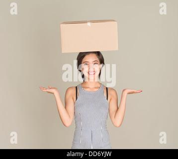 Junge Frau glücklich Gleichgewicht Karton auf dem Kopf - Stockfoto