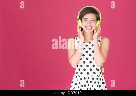 Schöne junge Frau multirassische Lachen und Musikhören mit grüne Kopfhörer - Stockfoto
