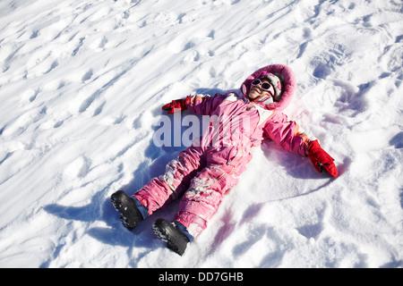 Gemischte Rassen Mädchen machen Schnee-Engel - Stockfoto