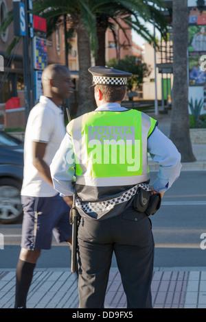 Rückseite der Polizist Policia lokal mit farbigen Mann zu Fuß passieren - Stockfoto