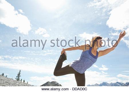 Reife Frau praktizieren Yoga auf Berggipfel - Stockfoto
