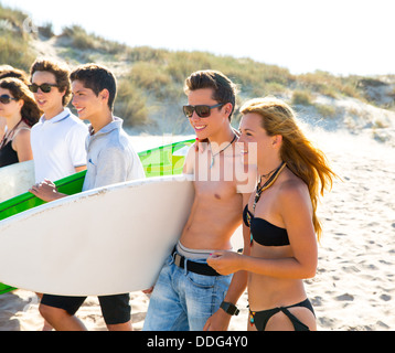 Surfer Teen jungen und Mädchen Gruppe zu Fuß am Strandsand - Stockfoto
