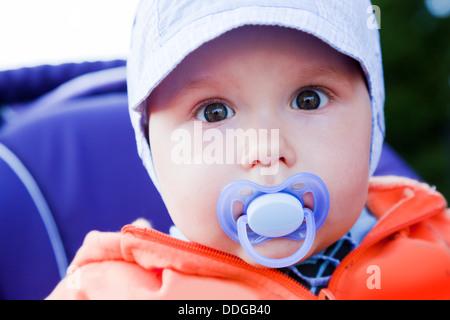 Junge baby Boy mit einem Dummy im Mund außerhalb in seinem Kinderwagen - Stockfoto