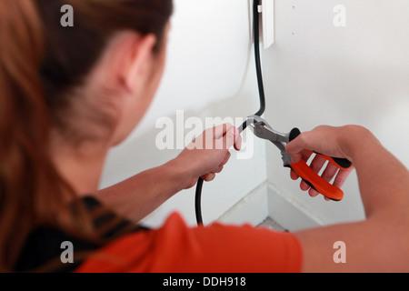 Elektriker einen Draht schneiden - Stockfoto