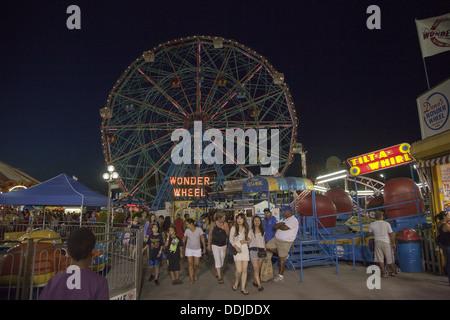Abend im Luna Park mit dem Wonder Wheel droht sich in den Hintergrund. Coney Island, Brooklyn, NY. - Stockfoto