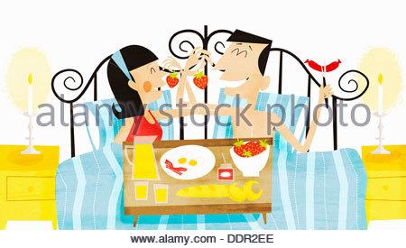 Glückliches Paar im Bett zu frühstücken - Stockfoto