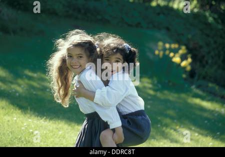 glücklich Schwestern in Schuluniform spielen Huckepack - Stockfoto