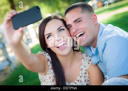 Happy Mixed Race paar Selbstbildnis mit einem Smart-Phone in den Park nehmen. - Stockfoto