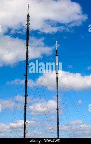 Zwei UK Fernsehen und Rundfunk Masten vor einem blauen Himmel mit Wolken. - Stockfoto