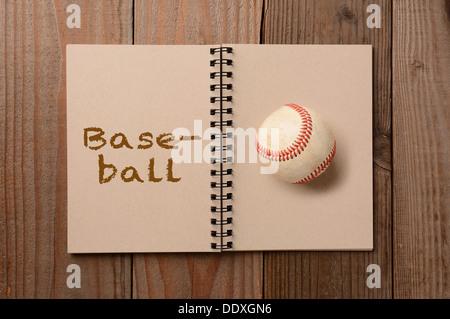 Ein abgenutzter Baseball auf die leere Seite eines Notebooks. Der gegenüberliegende Seite ist das Wort, das Baseball - Stockfoto