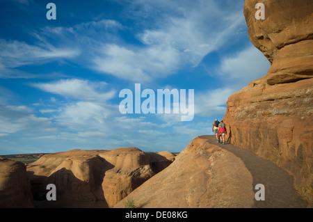 Junge Touristen paar Wandern auf dem Bergweg zum Delicate Arch, Arches-Nationalpark, Utah, Vereinigte Staaten von - Stockfoto