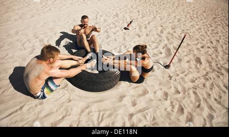 Fitness und gesunde Lebensweise. Kleine Gruppe von jungen Athleten, die Bauch-Übung mit einem LKW-Reifen am Strand zu tun. Sportler zu tun