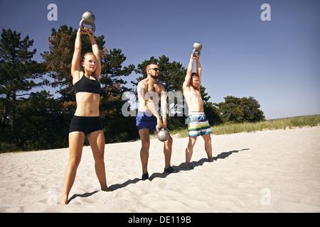 Gruppe von Athleten schwingen eine Wasserkocher Glocke über dem Kopf am Strand. Junge Menschen dabei Crossfit Training - Stockfoto