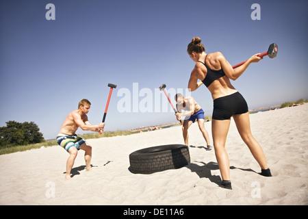 Drei starke Athleten tun Hammer Streik auf einem LKW-Reifen beim Crossfit Training draußen am Strand - Stockfoto