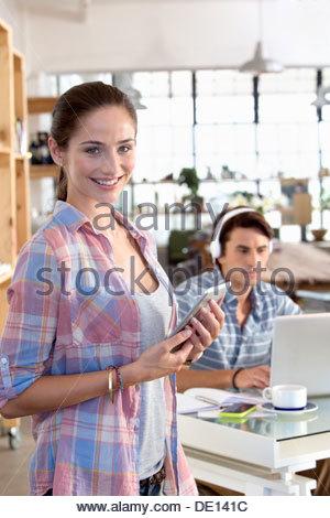 Porträt von lächelnden Frau mit digital-Tablette mit Mann Kopfhörer anhören und mit Laptop im Hintergrund - Stockfoto
