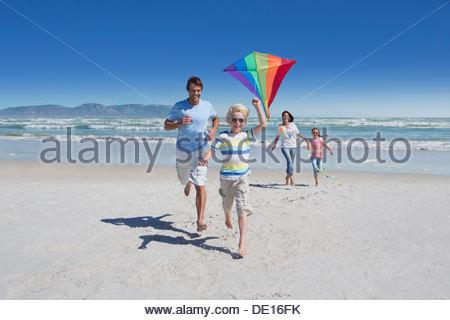 Glückliche Familie Drachen am Sonnenstrand - Stockfoto