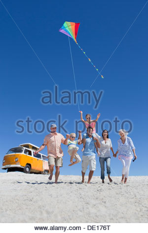 Glücklich mehr-Generationen-Familie mit Kite Wandern am sonnigen Strand mit van im Hintergrund - Stockfoto
