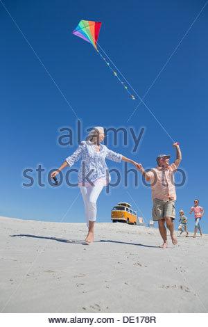 Großeltern und Enkelkinder mit Kite am sonnigen Strand mit van im Hintergrund laufen - Stockfoto