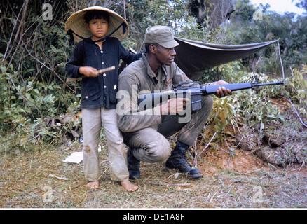 Vietnam war 1957 - 1975, vietnamesischer Junge neben einem amerikanischen nicht-beauftragten Offizier mit M16 Sturmgewehr, - Stockfoto