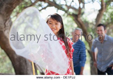 Lächelndes Mädchen spielen mit Schmetterlingsnetz - Stockfoto