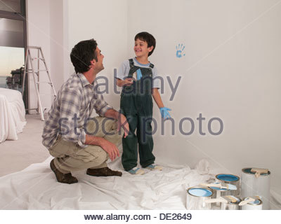 Vater Sohn machen Handabdruck auf Wand mit Farbe zu beobachten - Stockfoto
