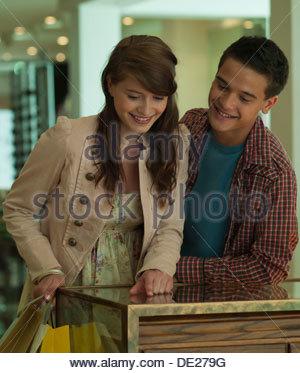 Lächelnde Teenager-Paar auf der Suche in Vitrine - Stockfoto