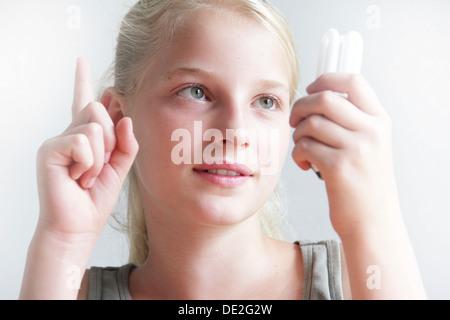 Mädchen hält eine Energie sparen Lampe in der Hand und hält ihr andererseits - Stockfoto