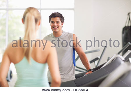Mann und Frau sprechen auf Laufbändern im gymnasium - Stockfoto