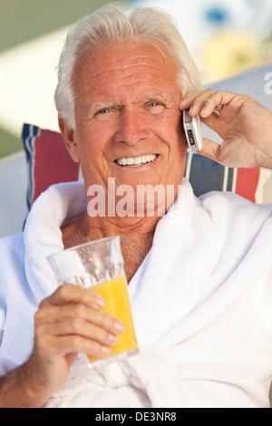 Attraktive gut aussehend senior glücklich im weißen Bademantel, draußen, Lächeln, reden auf seinem Handy Orangensaft - Stockfoto