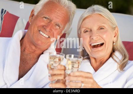 Ältere Mann und Frau Brautpaar auf Kur im weißen Bademantel lächelnd und Champagner trinken - Stockfoto